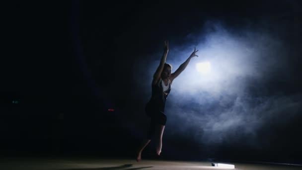 Fiatal nő tornász fut fel és egy front flip és a csavar végzi a levegőben az edzőteremben, a szőnyegen, a füst Steadicamnél lassítva