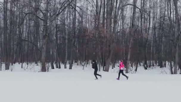 Man and woman in the winter running through the Park in slow motion.