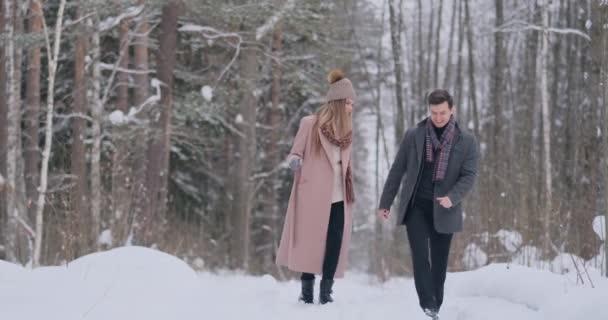 Mladý manželský pár v lásce chůze v zimním lese. Muž a žena se na sebe a smíchu v pomalém pohybu. Valentýna milostný příběh.