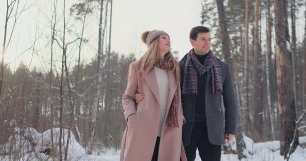 Young married couple in love walking in the winter forest. A man and a woman look at each other laughing and smiling in slow motion. Valentines Day love story.
