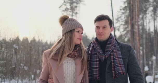 In the winter snowy forest, young men and women dressed in coats and scarves are walking and having fun. Loving couple spend together valentines day.