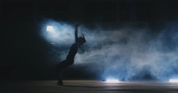 In slow motion in the smoke girl acrobat performs several back flips and coups in the air.