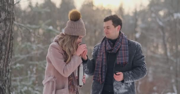 A caring man warms his wifes hands in the winter on the street in a snow-covered Park