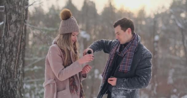 Verliebte Paare im Winterwald, um Tee aus der Thermoskanne zu trinken. Stylische Männer und Frauen im Mantel im Winter im Park spazieren gehen.