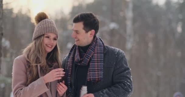 schöne und stylische Paar Hipster in Mantel und Schal trinken Tee aus einer Thermoskanne im Winterwald nach einem Spaziergang. Liebesgeschichte