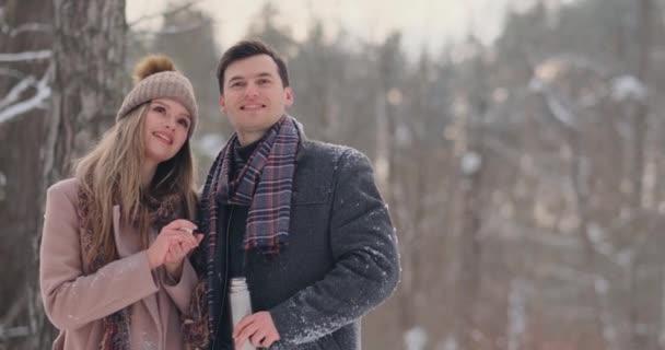 Glückliches Paar heißen Teetassen über verschneite Winterlandschaft zu halten. Junges Paar in Liebe auf einen Winterurlaub, stehen neben einem Baum und heiße Tasse Tee trinken