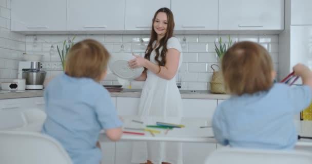 Mama in der Küche spült Geschirr und zwei Söhne sitzen an einem Schreibtisch und zeichnen mit Buntstiften auf Papier. junge Familienmutter lächelt und schaut Kinder an