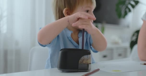 Boy sharpening a colored pencil in a sharpener sitting at the kitchen table