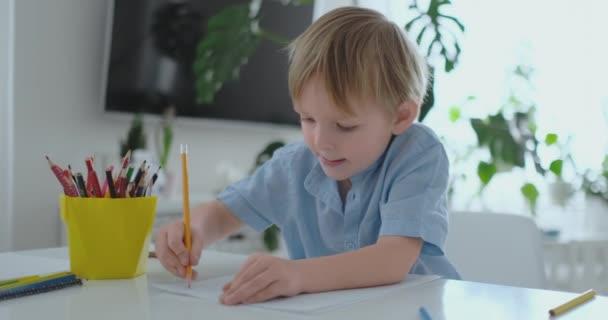 Malé dítě sedí u stolu kreslí tužkou, kresba malba v různých barvách