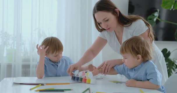 Mom helps her sons to develop creative skills and is engaged with them to create drawing paints with the help of fingers. Child development. Creative family. Loving mom