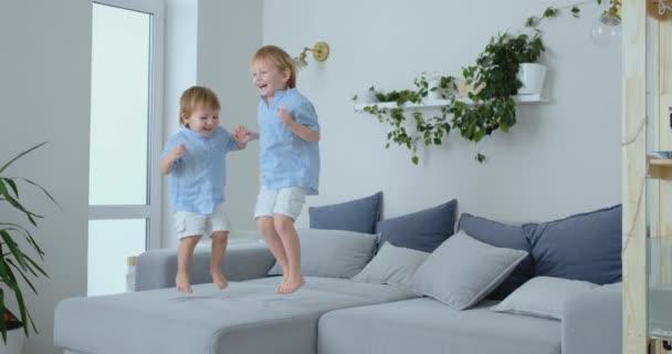 Due fratelli di ragazzini sono saltare sul divano e divertirsi. Gioia, risate e divertimento a casa. Infanzia felice