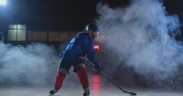 Profesionální hokejista s holí urychluje na ledě a náhle přestane před kamerou dívá přímo do kamery
