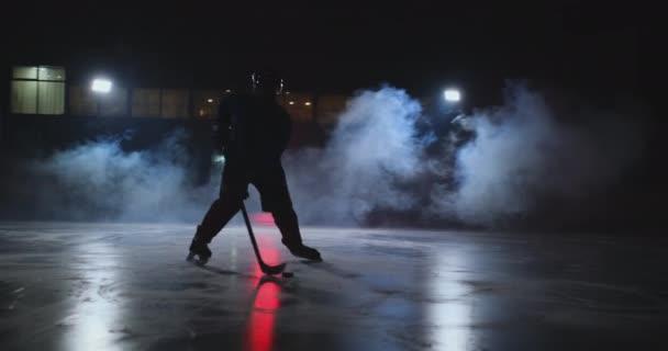 Mužské hokejista s PUK na ice Areně ukazuje, driblování pohybující se přímo do kamery a dívat se přímo do kamery na tmavém pozadí v kouři