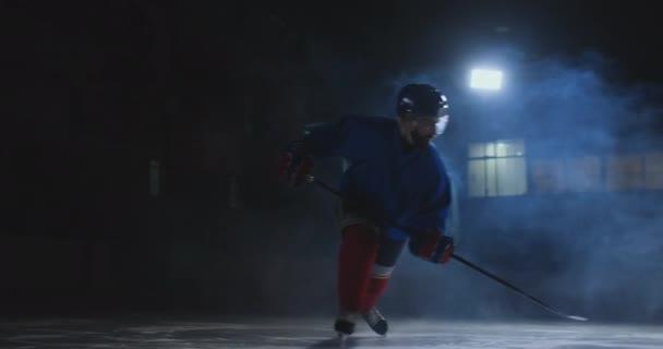 Muž hokejista s PUK na ledě v podobě hokej listy s holí v ruce ze tmy a dívá se přímo do kamery