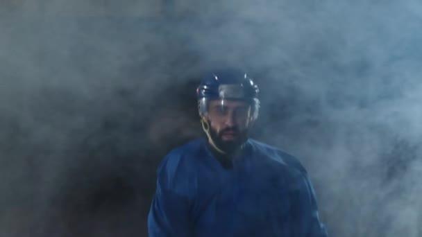 Profesionální hokejista s holí a PUK se pohybuje na Luda na brusle a helmu na tmavém pozadí a kouř. Dribling s pukem mladého muže v ice Areně