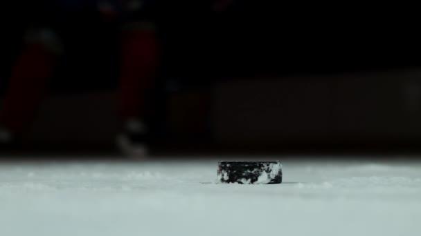 Létající sněhu na ledě a Close-up zpomalené hokejový puk, hokejový brankář nabere PUK holí