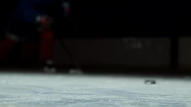 Detail PUK je na ledě a v pomalém pohybu hokejista vytáhne nahoru a sníh létá do kamery a si bere PUK holí