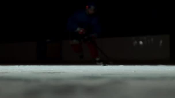 Detail zpomalené hokejový puk a létající sníh, hokejista nabere PUK holí