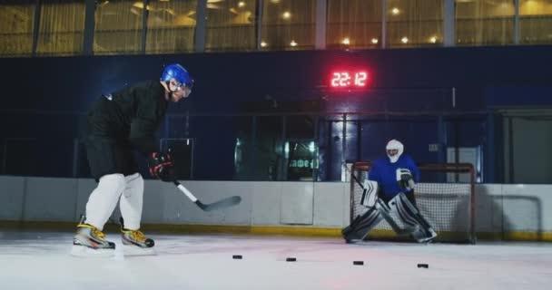 Profesionální hokejový hráč a brankář vlak děrování PUK na branku. Brankář a hráč v tréninku. Zpomalený pohyb