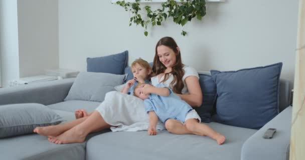 Maminka objímá své dva malé syny na gauči v obývacím pokoji a sleduje televizi. rodina sledování televize