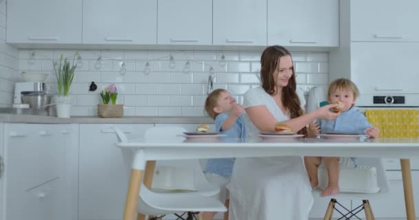 Mum with two young sons is eating burgers at home