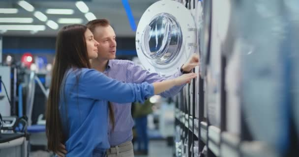 Das junge Ehepaar Mann und Frau im Haushaltswarengeschäft entscheidet sich, eine Waschmaschine für das Haus zu kaufen. öffnen Sie die Tür mit Blick in die Trommel, vergleichen Sie das Design und die Eigenschaften der Geräte.