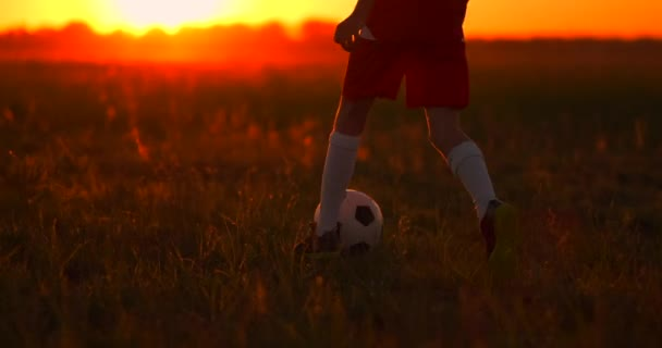 Tracking a boy football player running with a ball at sunset in the field