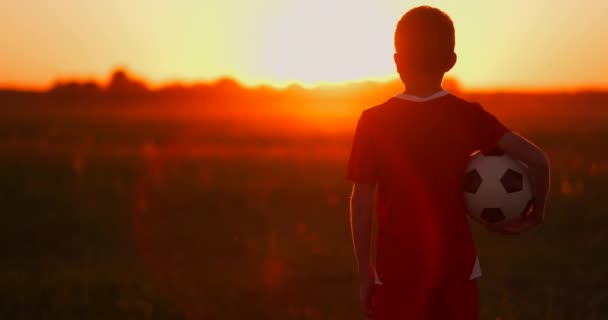 boy with a ball in a field at sunset, boy dreams of becoming a soccer player, boy goes to the field with the ball at sunset