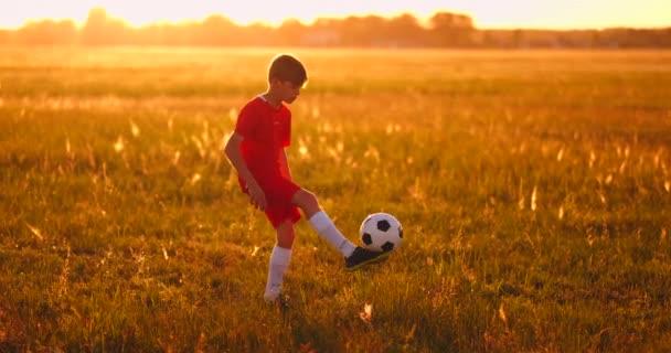 Mladý chlapec fotbalista při západu slunce žonglování s míčem v poli