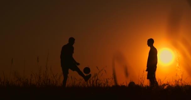 Dva chlapci hrají fotbal při západu slunce. Silueta dětí hrají s míčem při západu slunce. Koncept šťastné rodiny