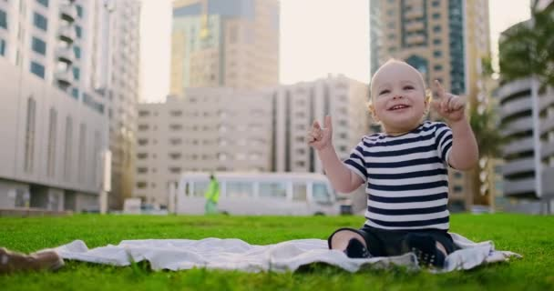 Happy small child sitting in grass with white daisies city background