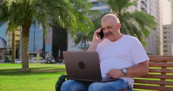 Senior sitzt im Sommer mit Laptop im Park und plaudert