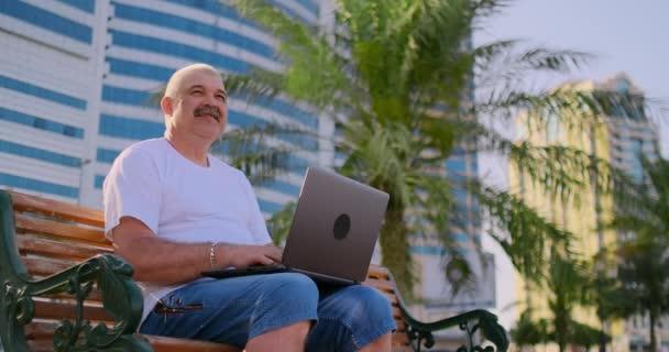 Senior im weißen T-Shirt sitzt im Park auf einer Bank unter Palmen und blickt auf den Laptop-Bildschirm