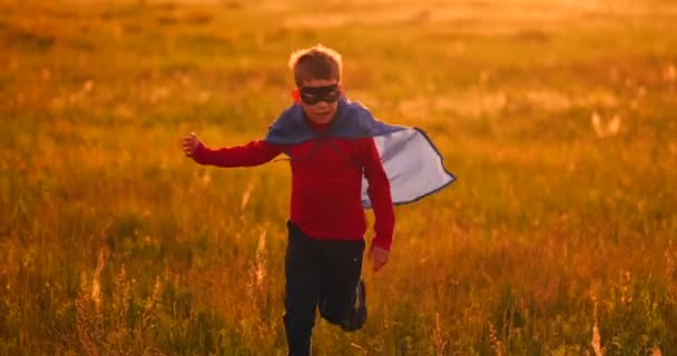 Little superhero boy in the field at sunset fantasizes and dreams.