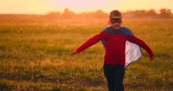 Fiú a szuperhős jelmez-és maszk fut át a területen naplementekor álmodik és fantasizing
