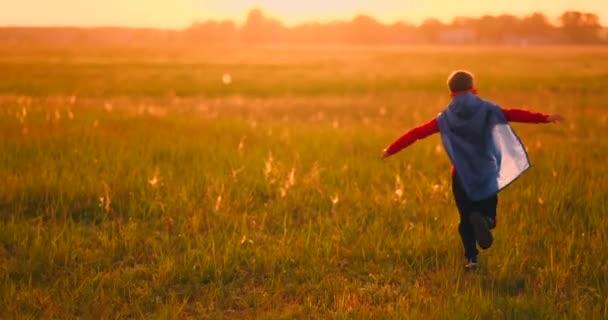Kis szuperhős fiú a területen naplementekor fantáziál és álmok
