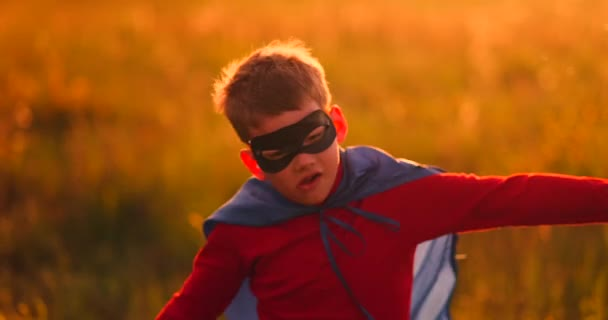 Boy in superhero costume and mask running across the field at sunset dreaming and fantasizing