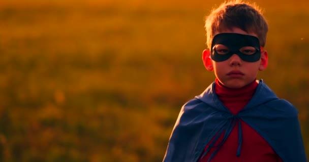 A fiú a maszk és a Cape egy szuperhős napnyugtakor a területen