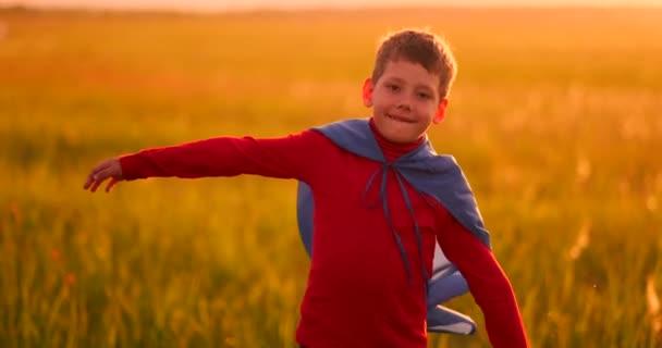 Kisfiú játszik, és az álmok egy szuperhős a naplementekor