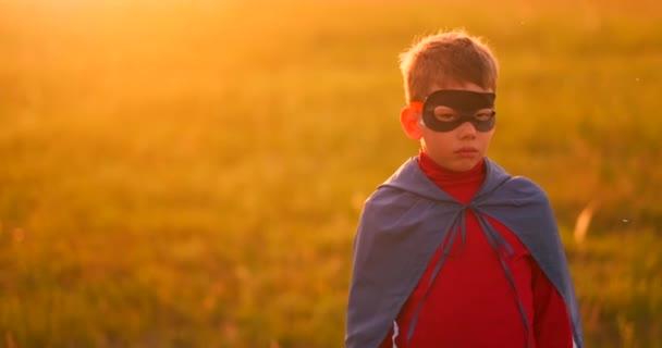 A gyermek a ruha egy szuperhős, egy piros köpenyt fut át a zöld gyepen, a háttérben a naplemente, a kamera felé