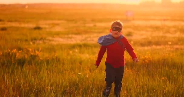 A fiú egy öltönyt, és egy szuperhős maszk fut át a területen naplementekor a fűben