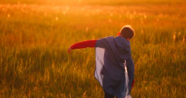 kleiner Superheldenjunge auf dem Feld bei Sonnenuntergang fantasiert und träumt.