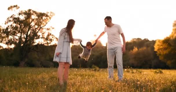 Maminka a táta potřásli dítěti, jak si hrají na rukách, chlapec je šťastný, když si hraje s rodiči na ulici v létě při západu slunce.