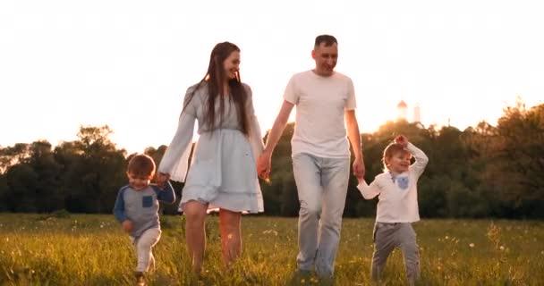 Šťastný rodinný muž se dvěma dětmi, kteří chodí po hřišti při západu slunce v záři slunce v létě v teplém počasí