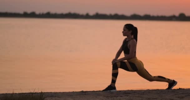 Woman is making lunges and crouching outdoors, training her body. Young slim woman is working muscles of her legs, hips and buttocks