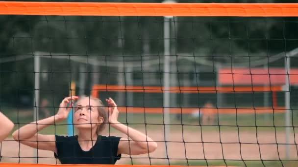 Pomalý pohyb, zavřít, nízký úhel: neidentifikovatelný mladý ženský ruce hrající volejbal na netu. Útočný hráč hřeje míč a protivník ho blokuje přímo nad sítí během turnaje.
