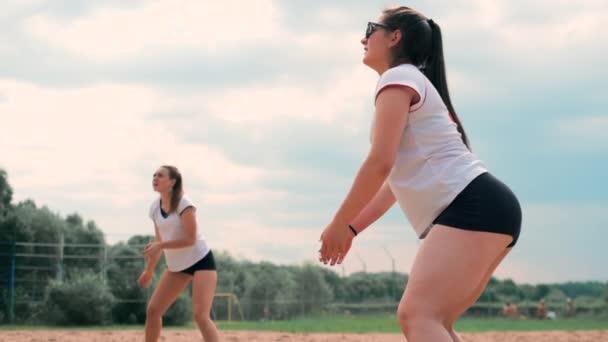 Čtyři holky hrajou volejbal na pláži. Plážový volejbal, síťky, ženy v bikinama. Plochá kreslená ilustrace. Začni hru, holka držící míč