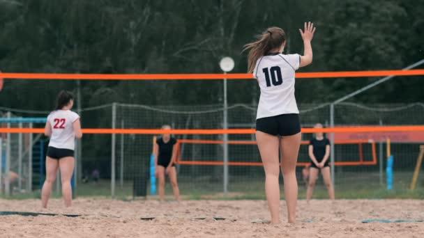 Profesionální volejbal slouží ženě na plážové turnaji. Volejbalové sítě hráč při aplikování pohledu zablokuje zobrazení