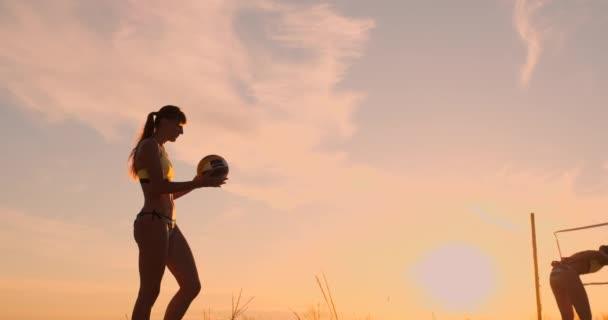 Atletická dívka, která hraje plážový volejbal ve vzduchu a udeří míč přes síť za krásný letní večer. Ta Kavkazská žena bodne