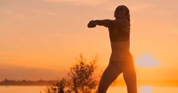 Středovýchodní volejbalová dívka v bikinách, která čeká na ples na nádvoří při západu slunce, dává průchod předloktí během zápalu na pláži v pomalém pohybu